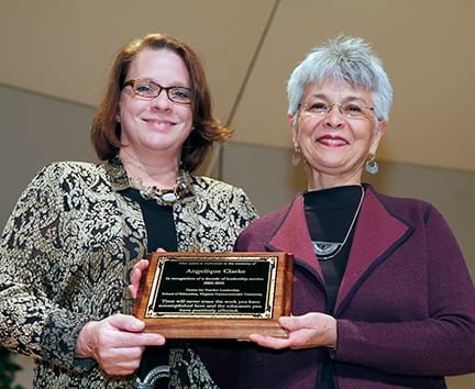 Holding a plaque in memory of Angelique Clarke are Stacey Branch, coordinator of the VCU Clinical Faculty Program, and Dr. Therese Dozier, director of the VCU Center for Teacher Leadership.