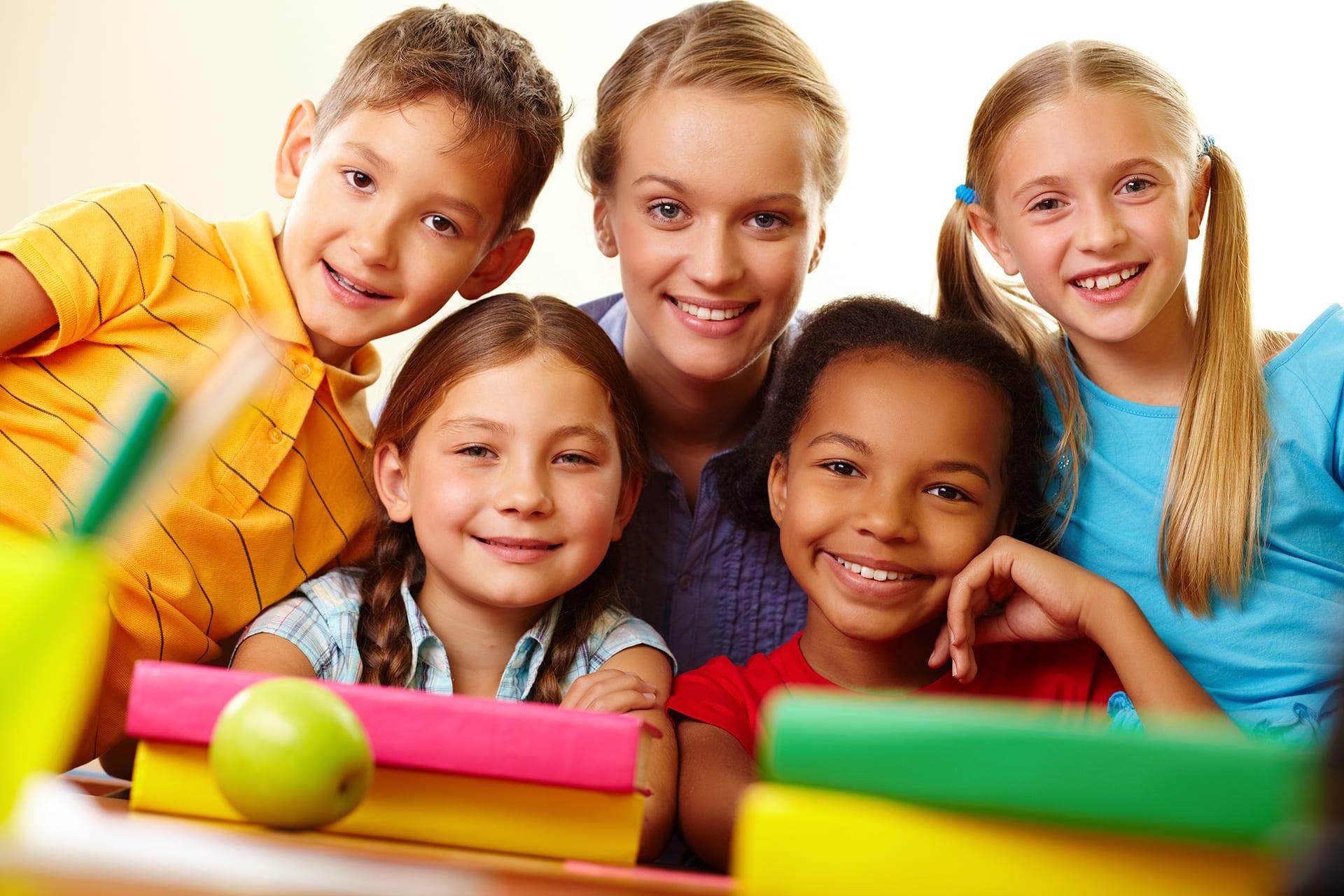 Portrait of smart schoolchildren and their teacher looking at camera in classroom