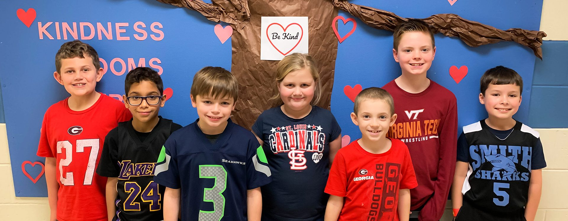 Seven students standing in front of a kindness tree display in the hallway.