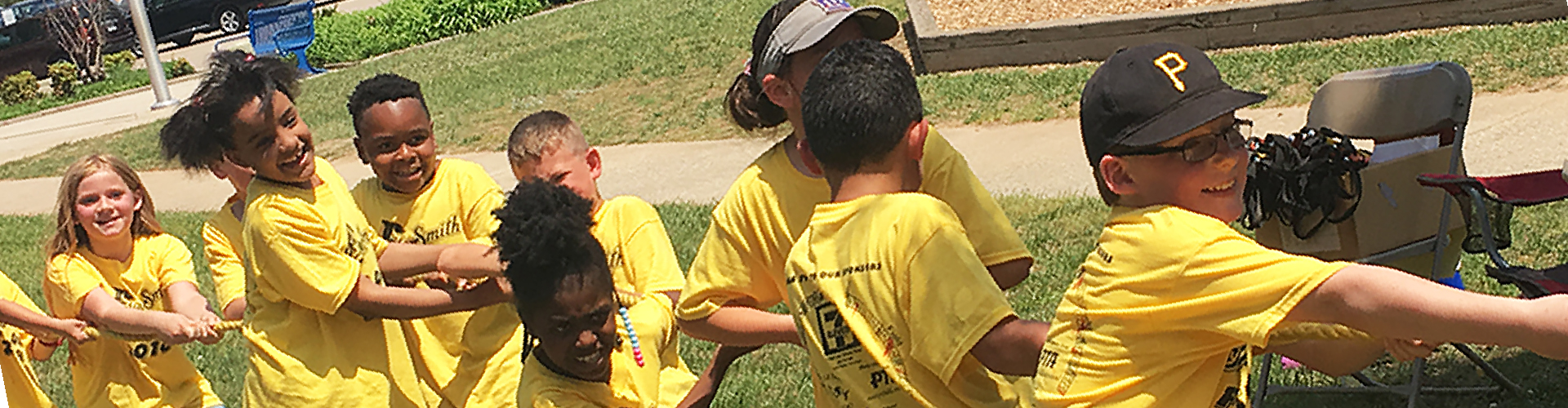 Students wearing yellow school spirit t-shirts pulling on a rope while playing tug-of-war.