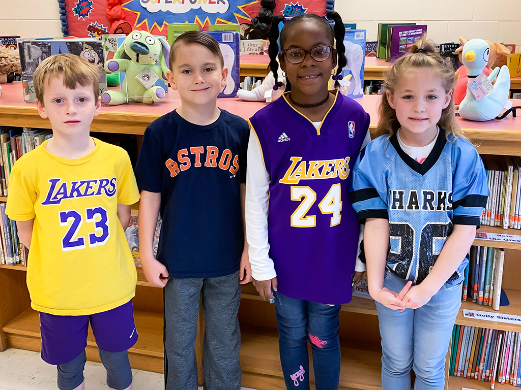Group of four students posing to show off their college team shirts.
