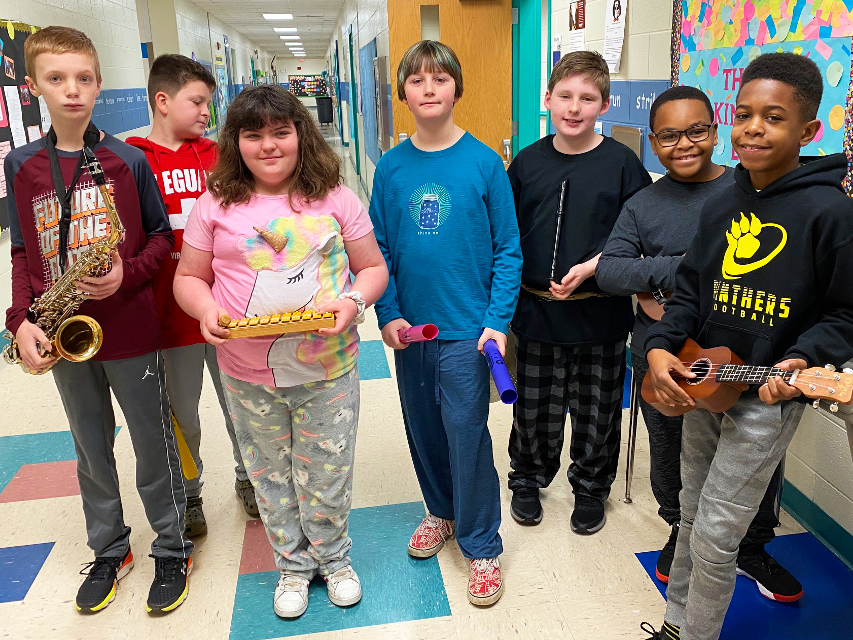 Seven students pose with musical instruments in the hallway.