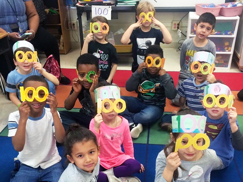 Students sitting on the floor wearing glasses they made out of paper that are shaped like the number 100.