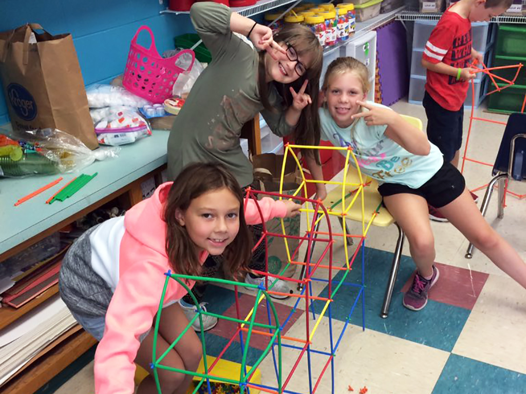 Three girls posing silly while building a giant model with sticks.