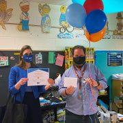 Teacher holding balloons & representative holding certificate.