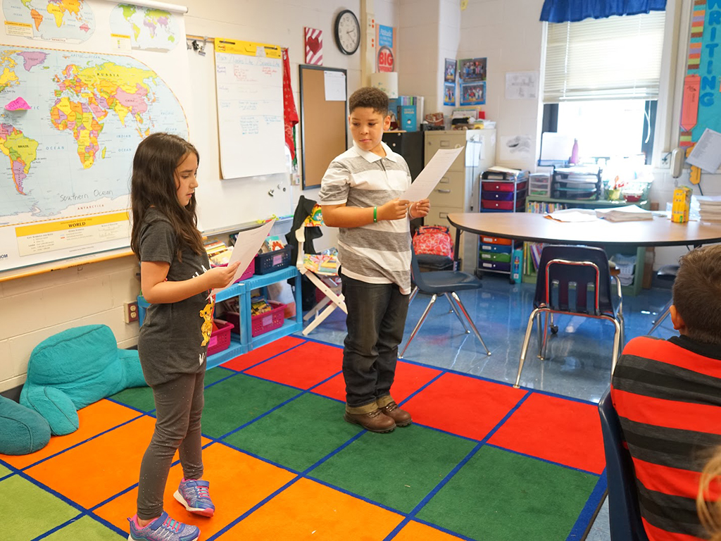 two students stand in front of class reading from a paper
