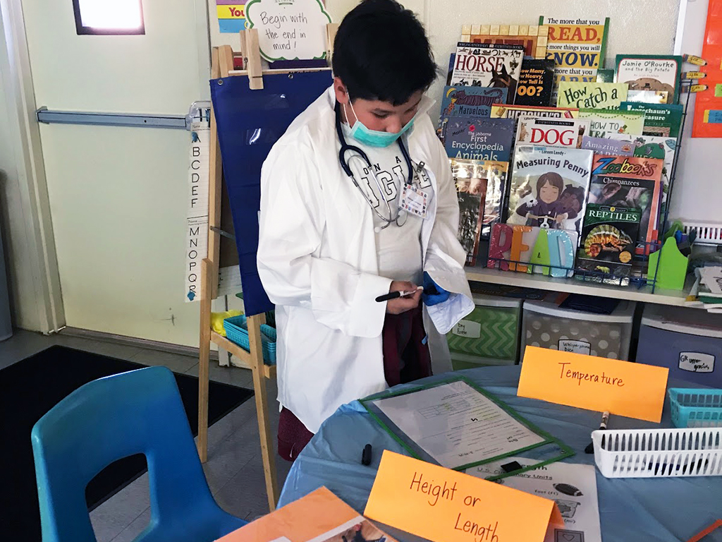 student dressed up like a doctor setting up his health station