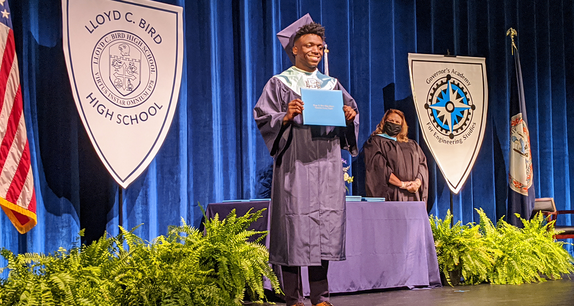 A male student on stage in cap and gown holding up his diploma with principal looking on in background.
