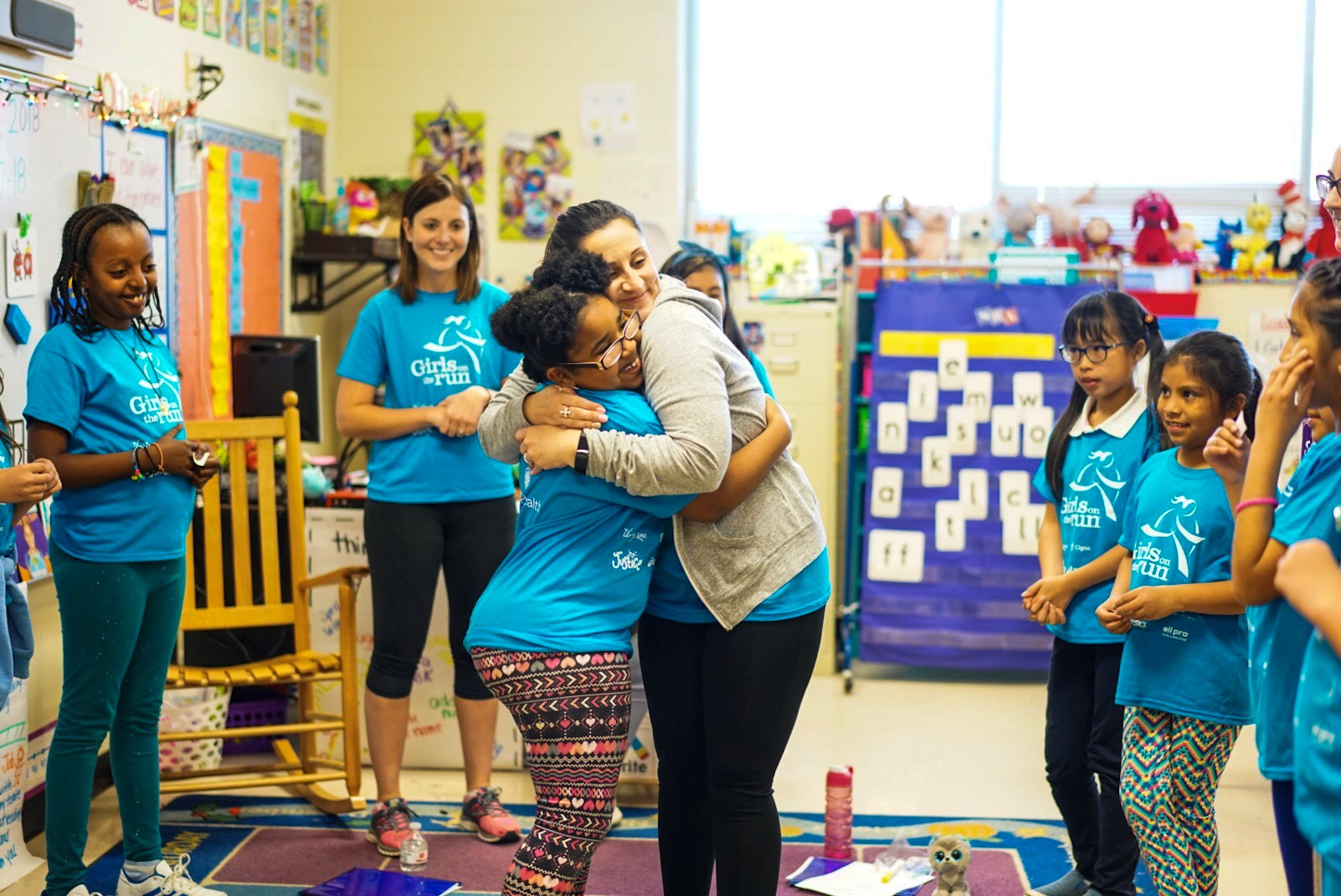 program leader hugging a member while other girls circle around them