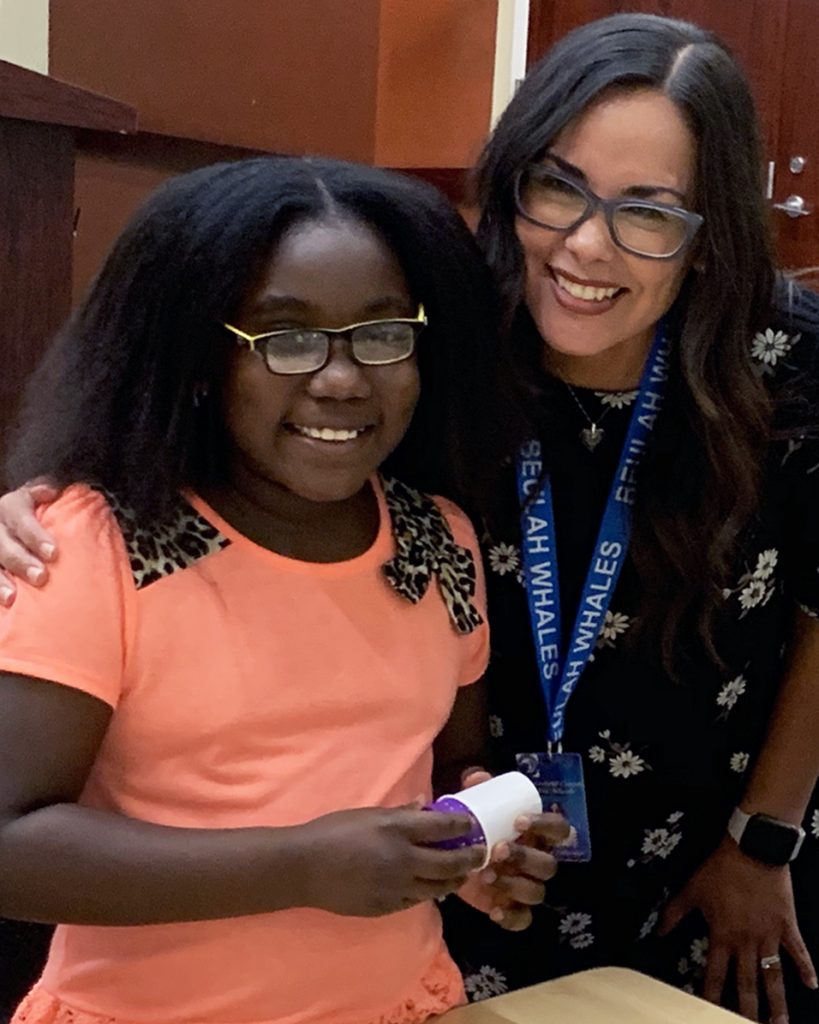 Assistant Principal poses with young female student