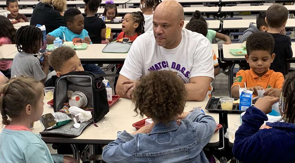 Dad sitting at the lunch table with several kids