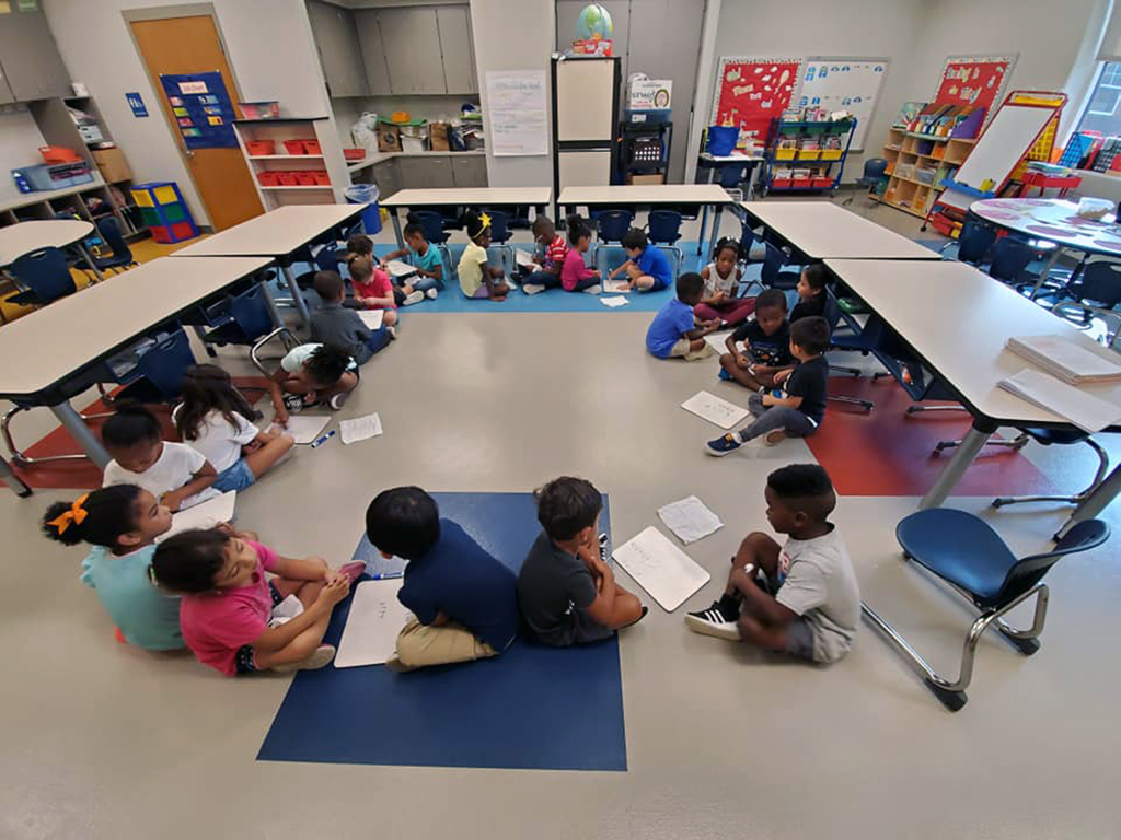 class sitting on floor in circles each talking to their partner