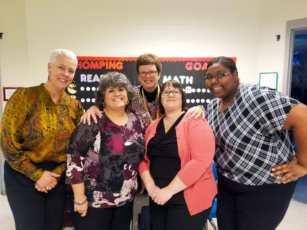 Group of five teachers pose for a group photo in a hallway.