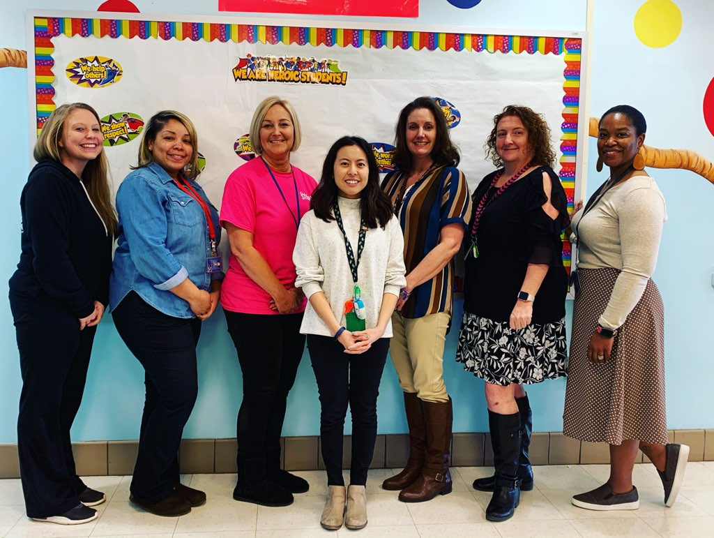 Seven teachers pose for a photo in front of a sign in the hallway.