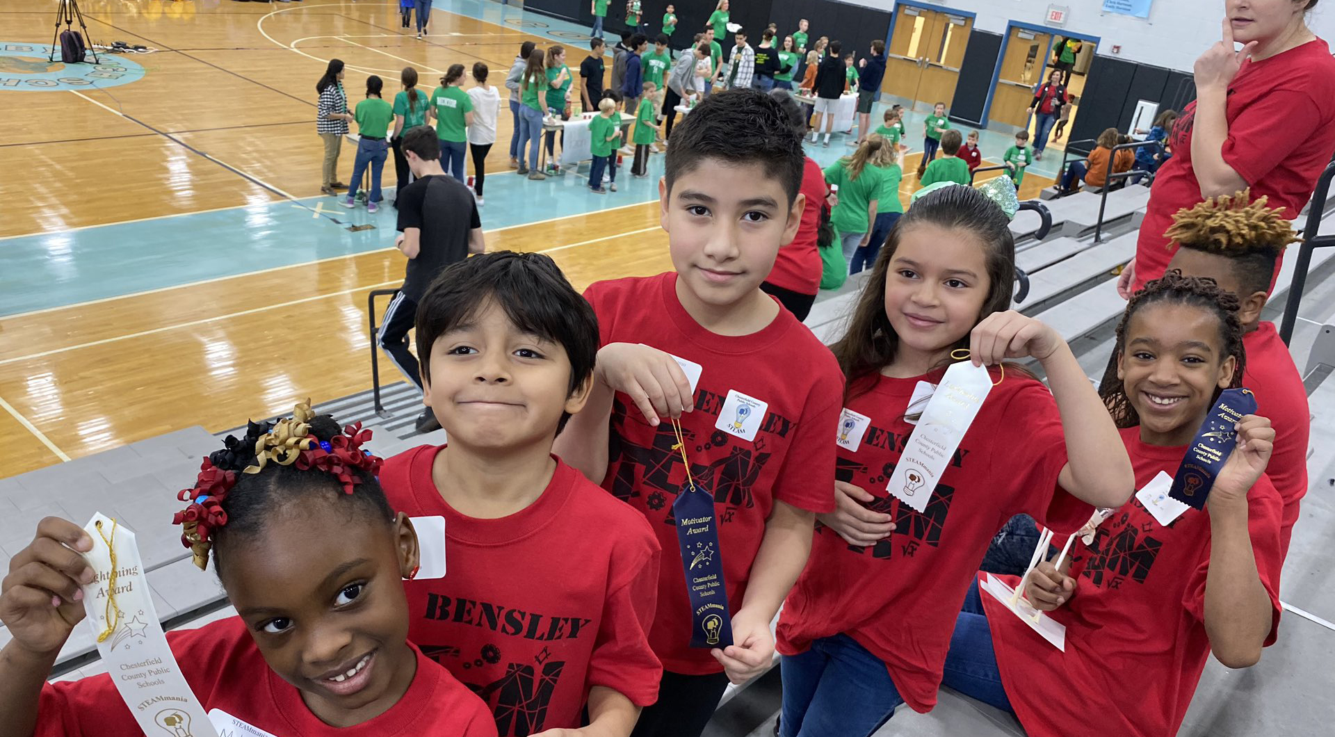 Group of students in matching red t-shirts hold up their awards at the STEAM competition.