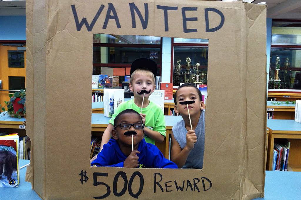 Three students holding mustache wands above their lips while standing behind a 'wanted $500 reward' frame.