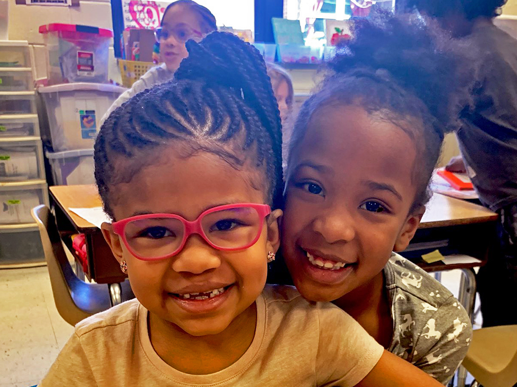 Two female students lean in for a photo with bright smiles.