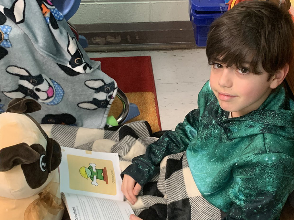 male student sitting on floor with blanket and stuffed animal reading a book.