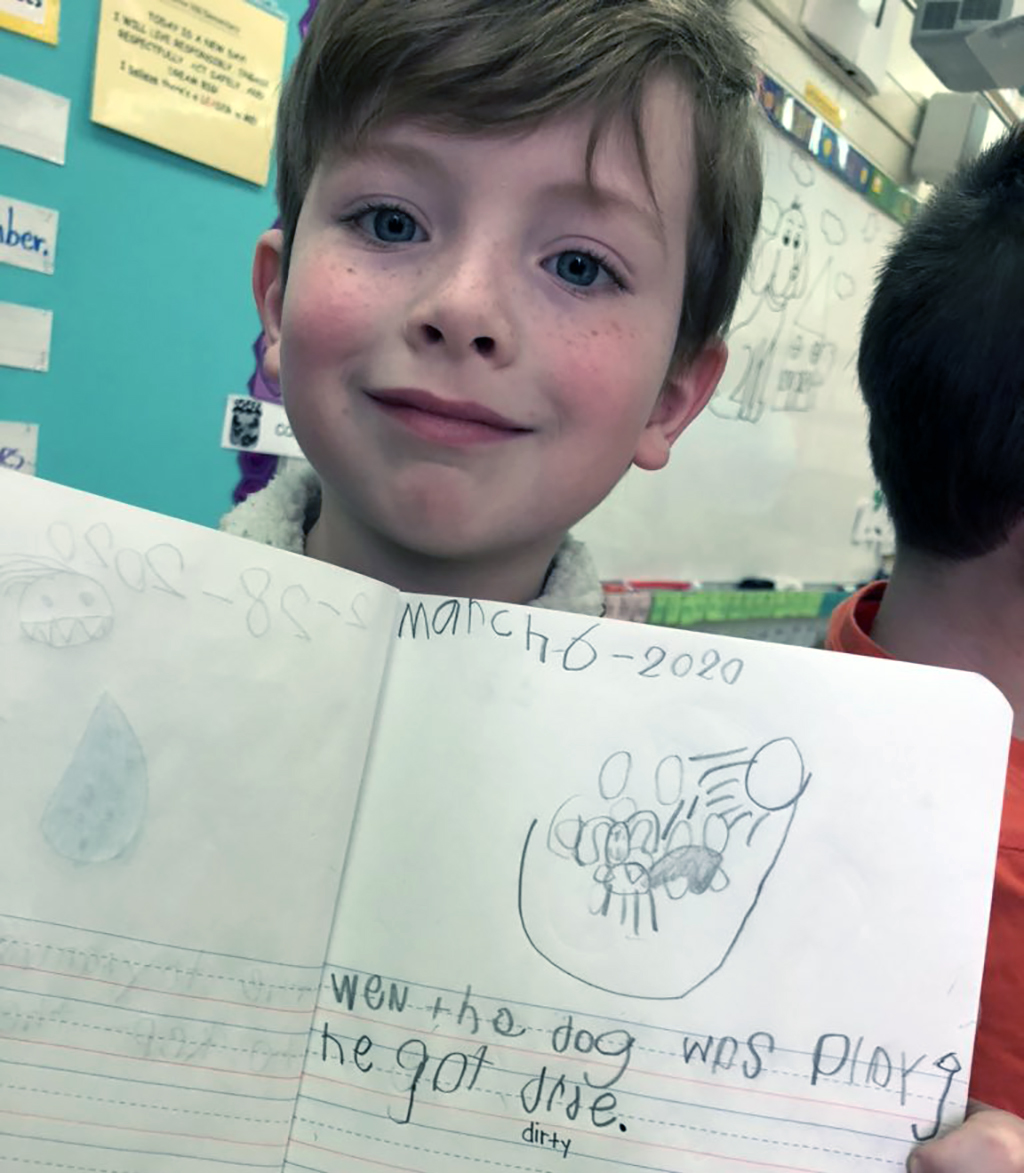 Male student holding up his journal page to see what he wrote.