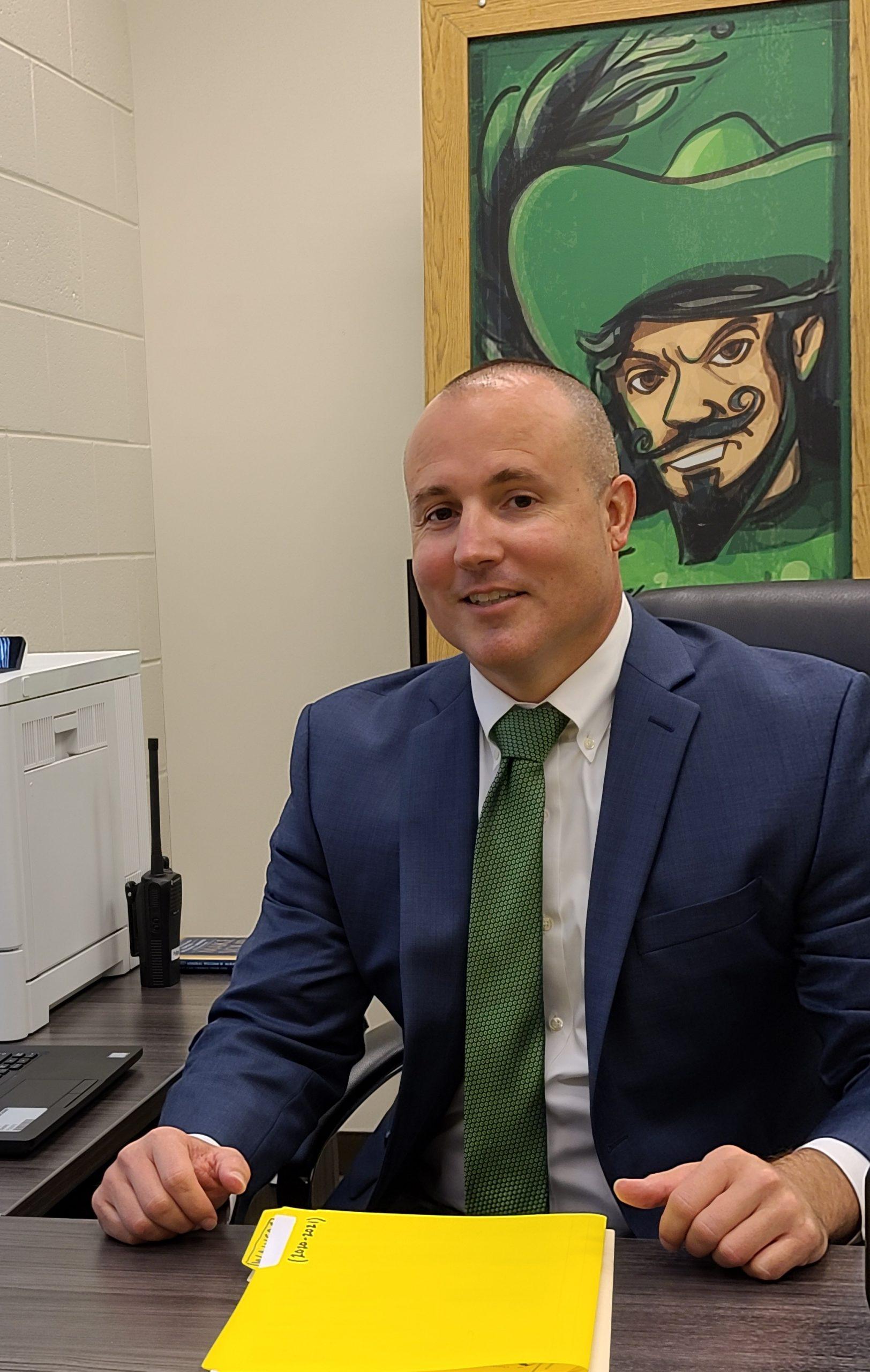 Principal sitting at his desk.