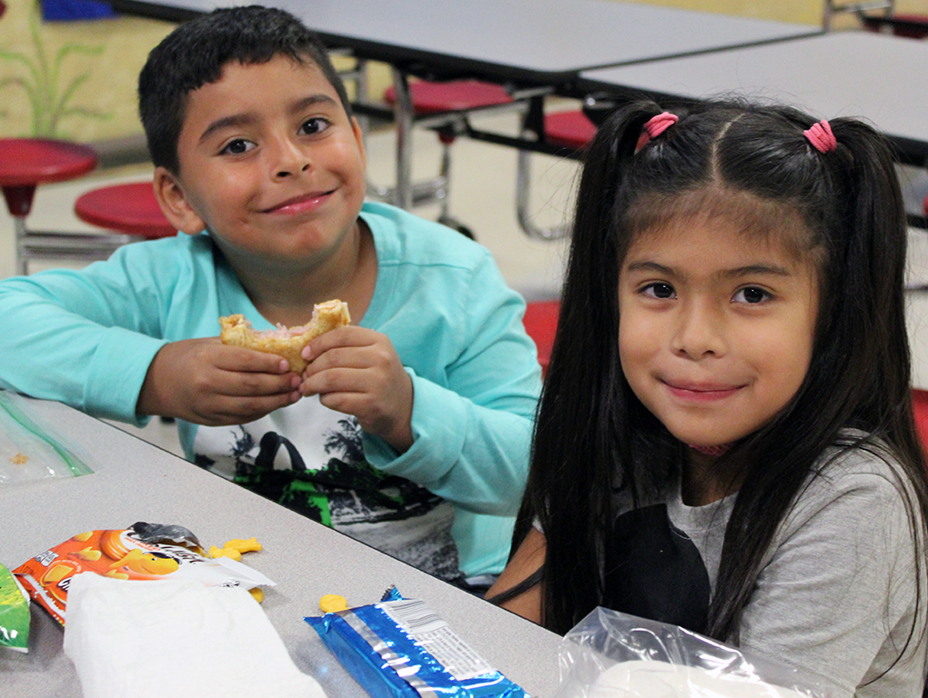 a boy and a girl eating at cafeteria table and smiling for the camera