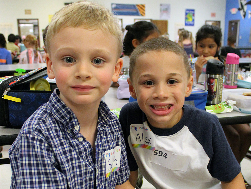 two boys smile for the camera in the lunchroom