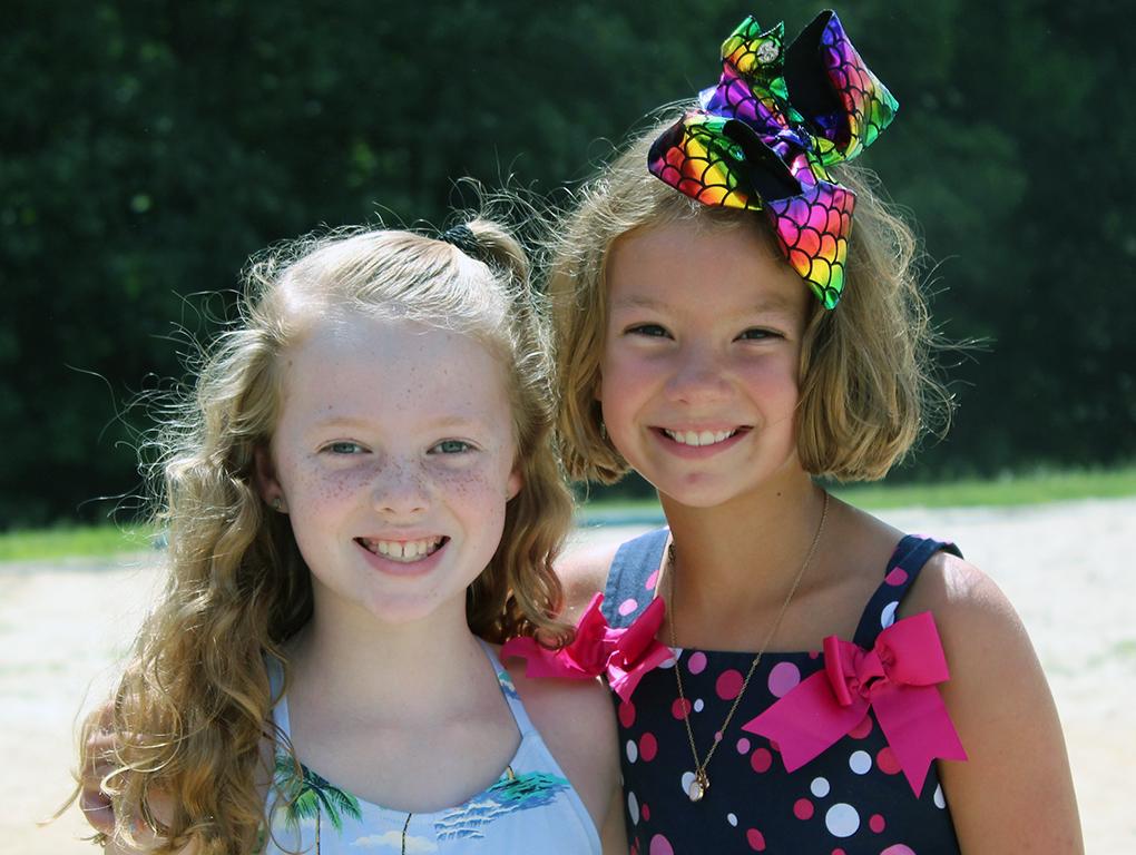 two girls hug and smile for camera