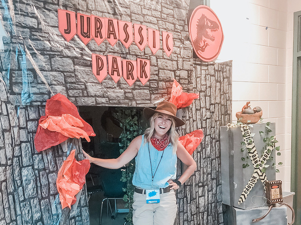 teacher standing in front of Jurassic Park background
