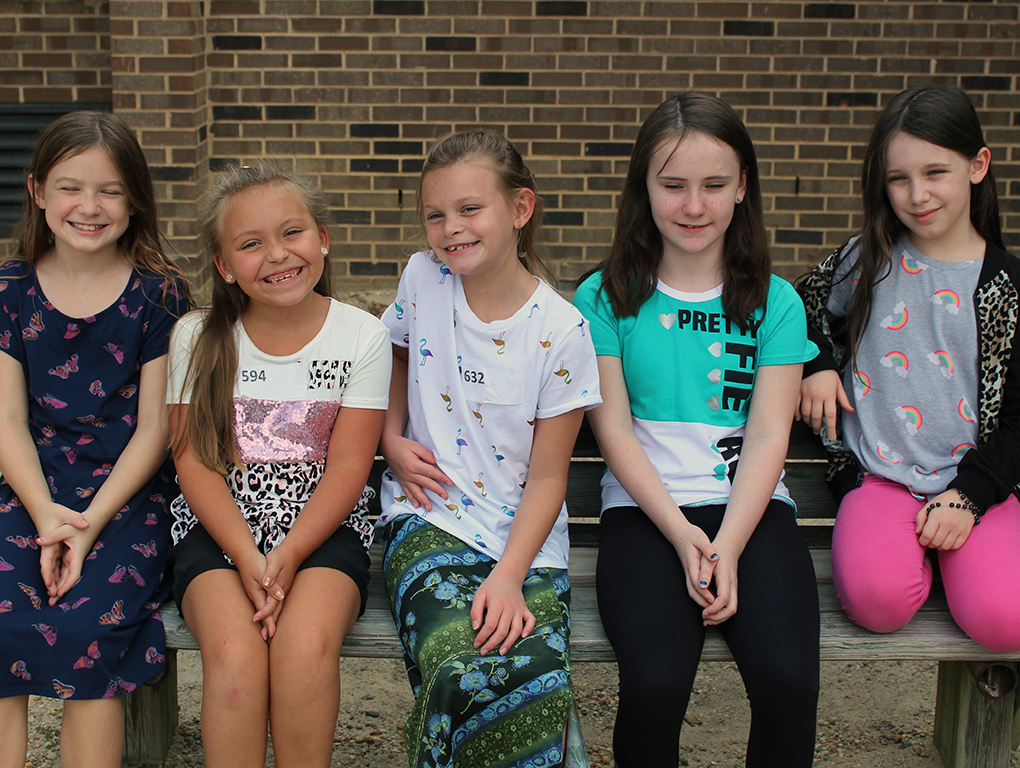 five girls sitting on a bench smiling for camera