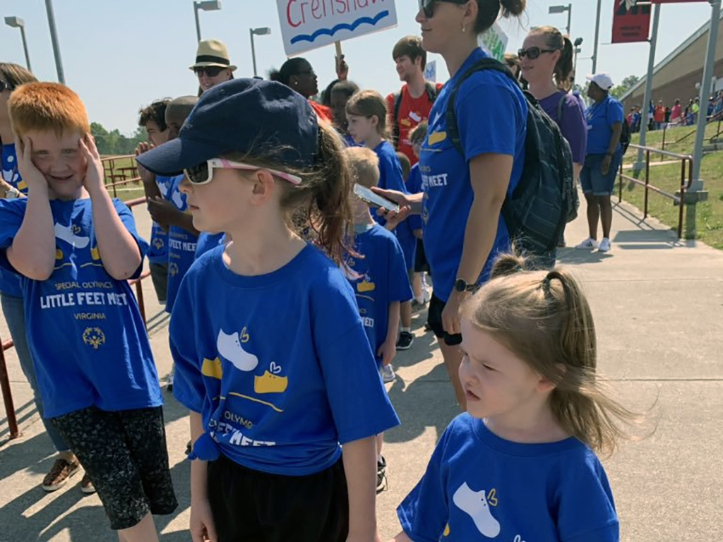 group of children all wearing blue t-shirts lining up for the little feet run