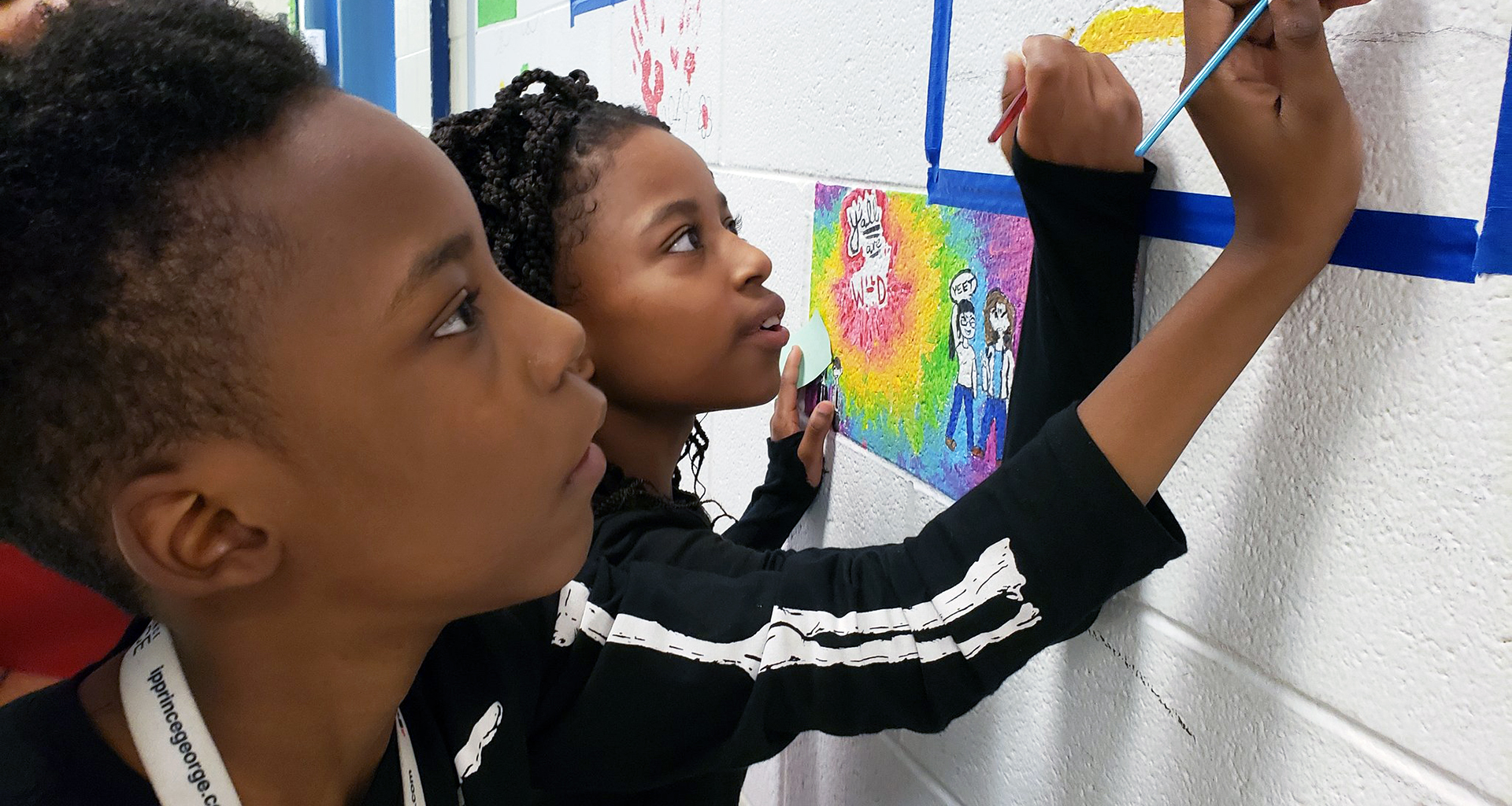 Two students painting a block on the hallway wall.