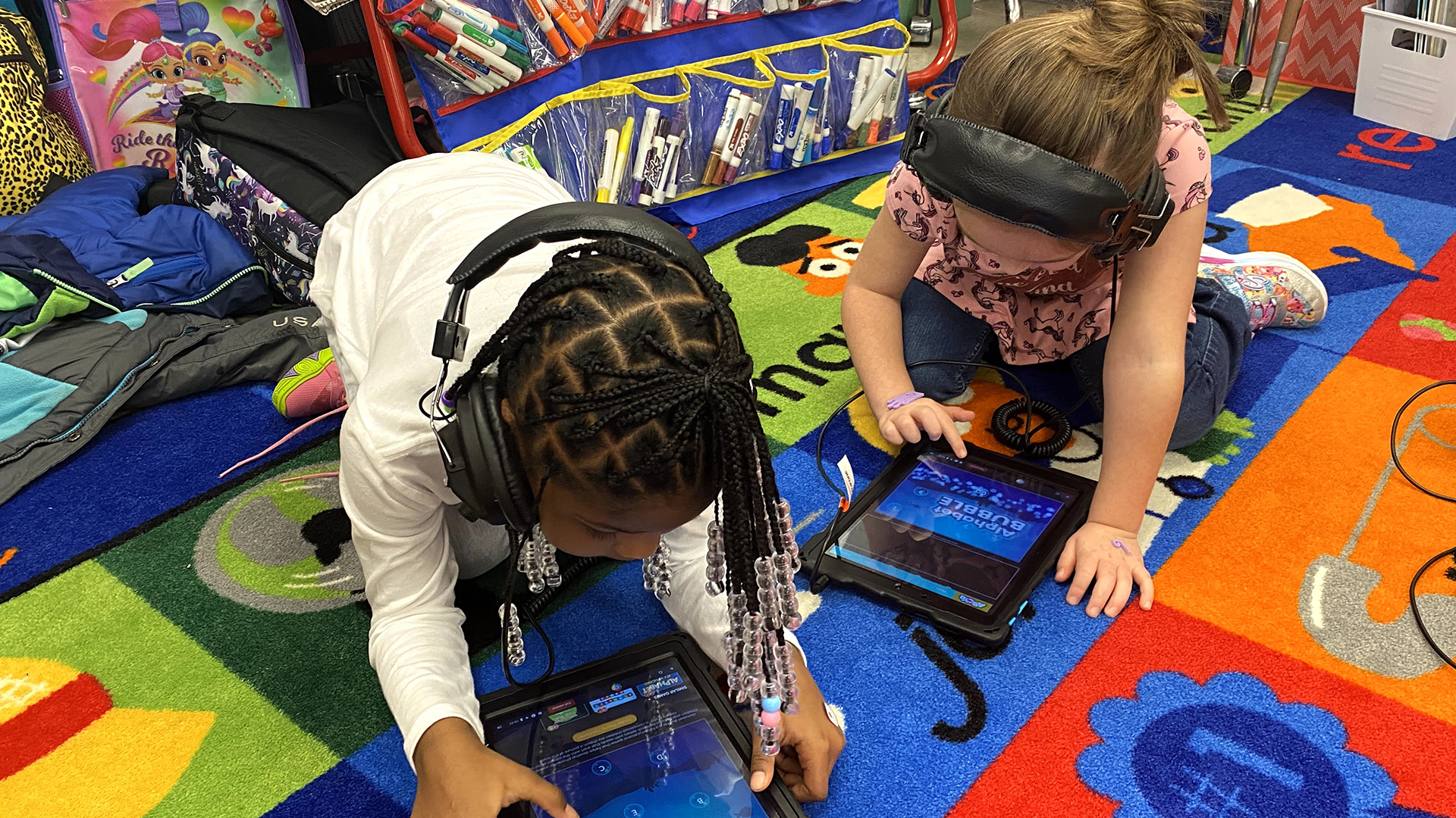 Two students on floor looking at a tablet device with headsets on.