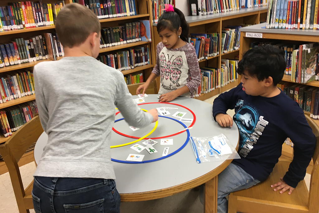 three students playing a game at a table in the library