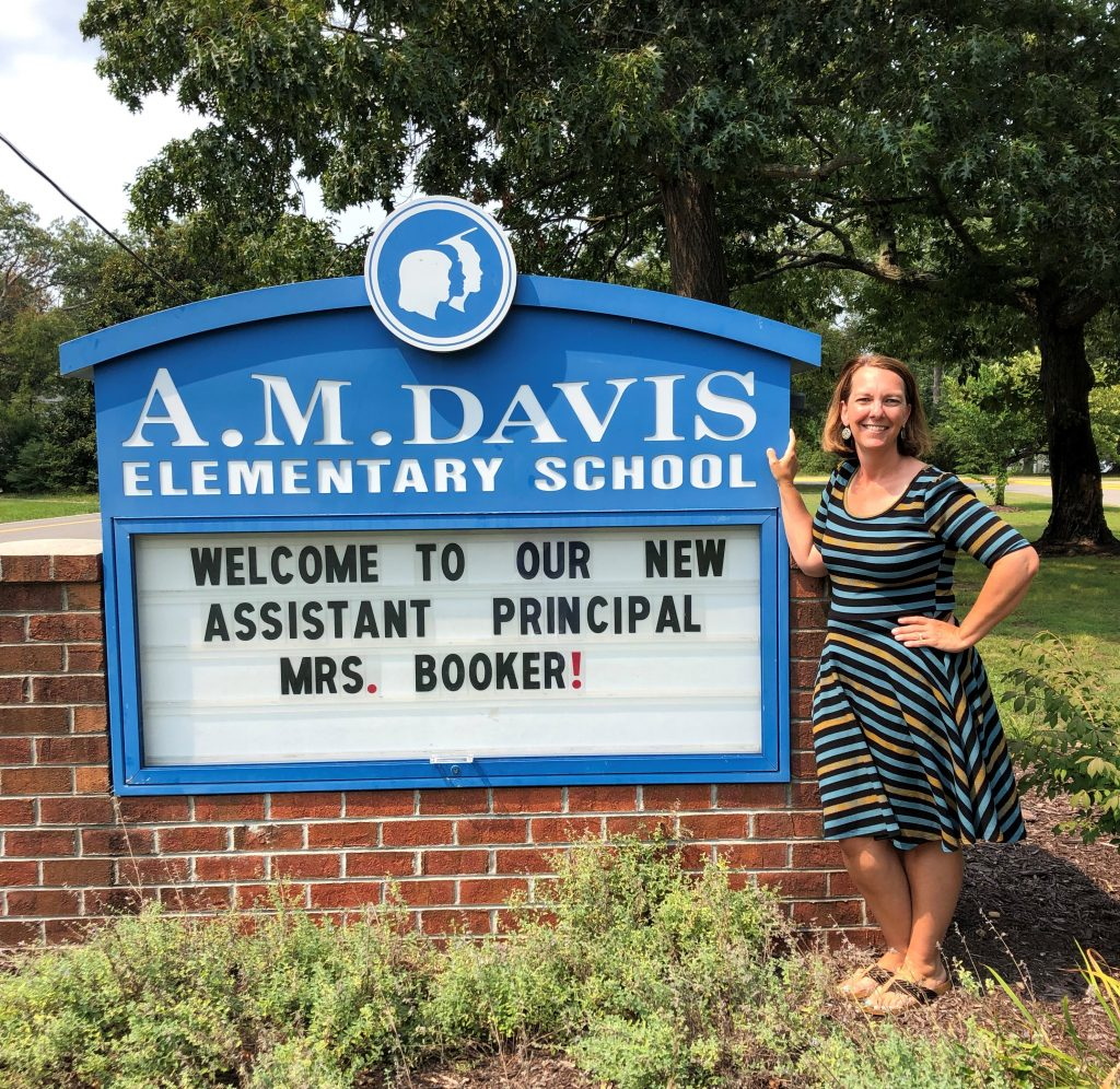 Mrs. Booker standing in front of welcome sign outside.