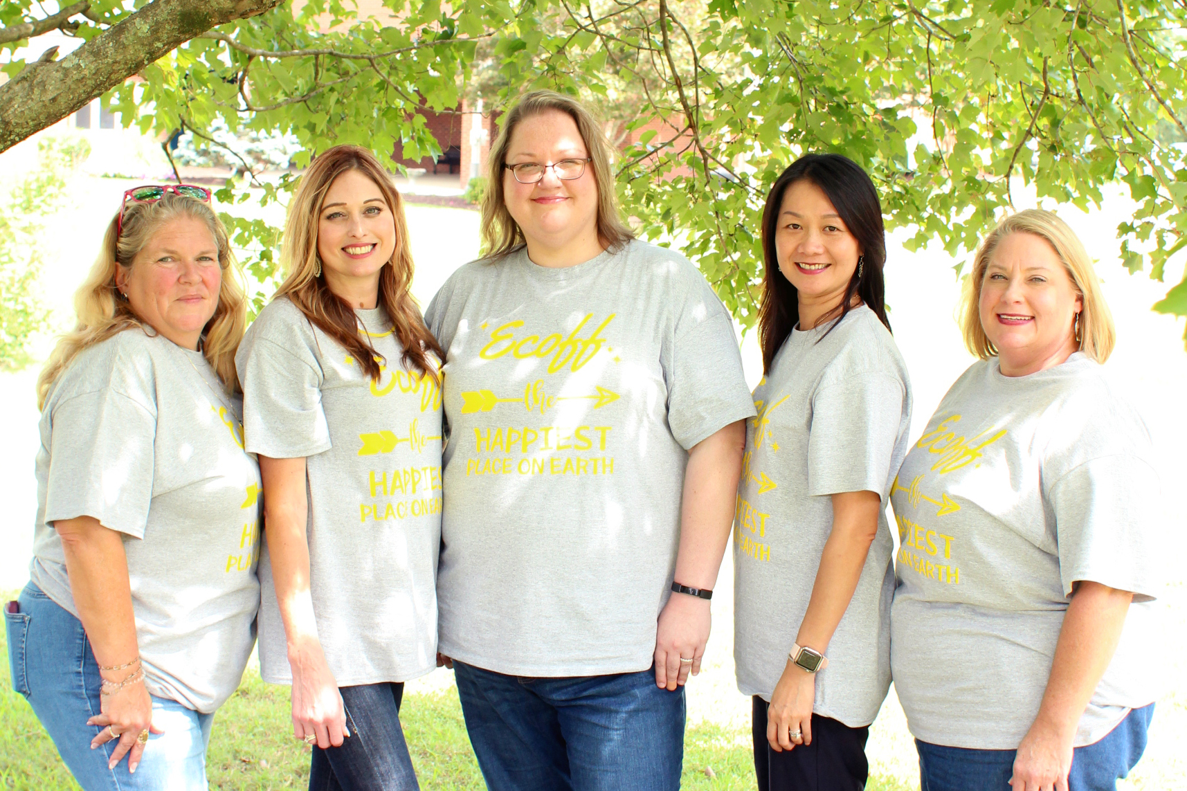Five female teachers posing around a tree.