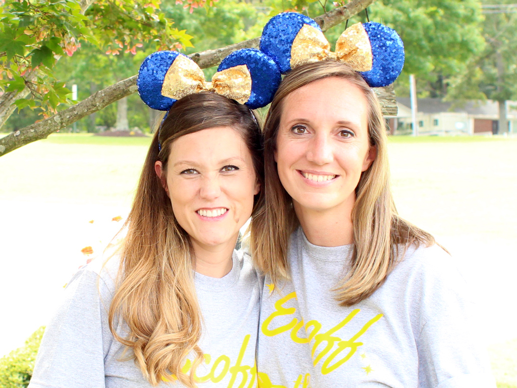 Two administrators pose together wearing mickey mouse ears.
