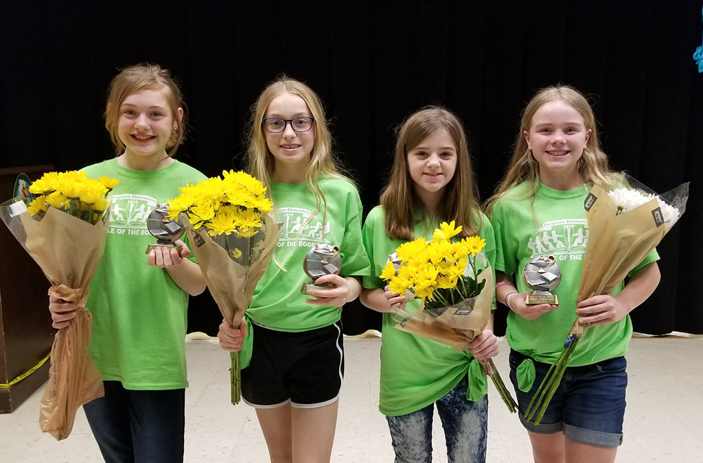 Four girls. Winners of Battle of the Books. Pose for a photo holding flowers.