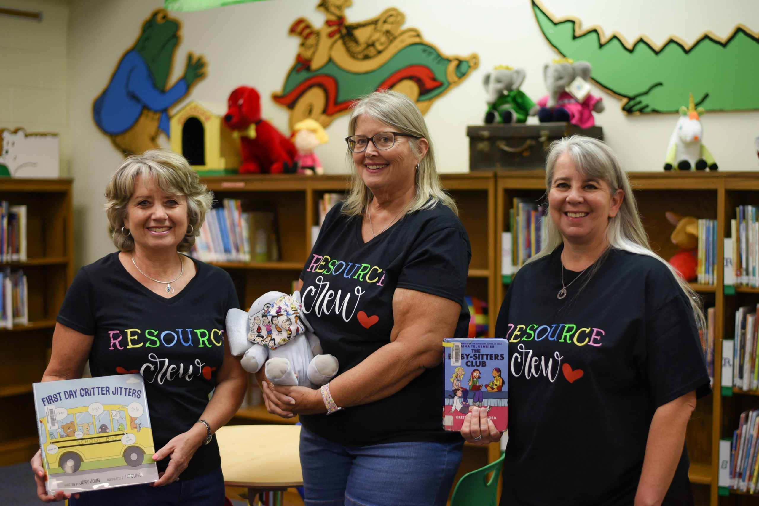 Three librarians pose holding books.