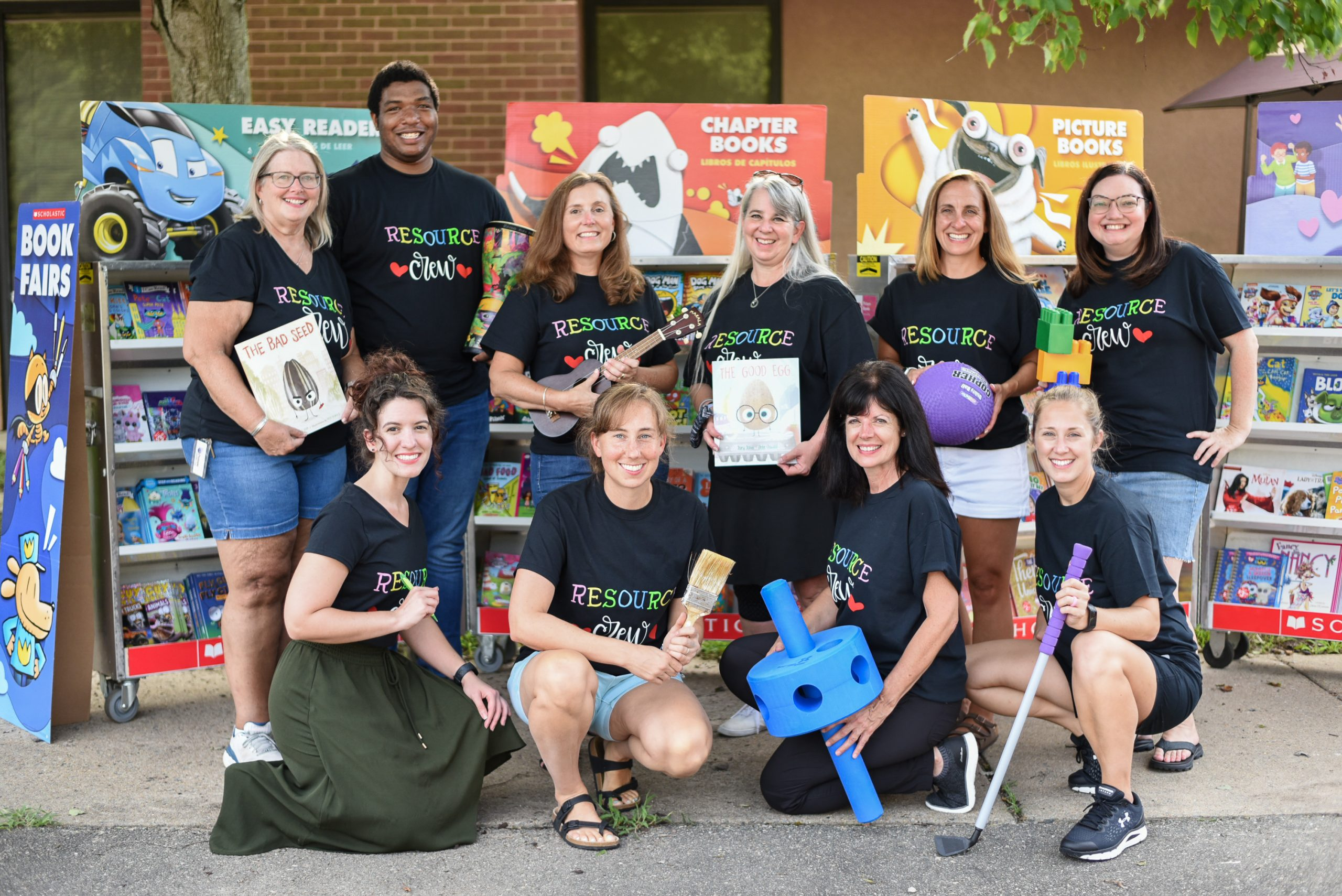 A group of resource teachers holding something that represents what they teach.