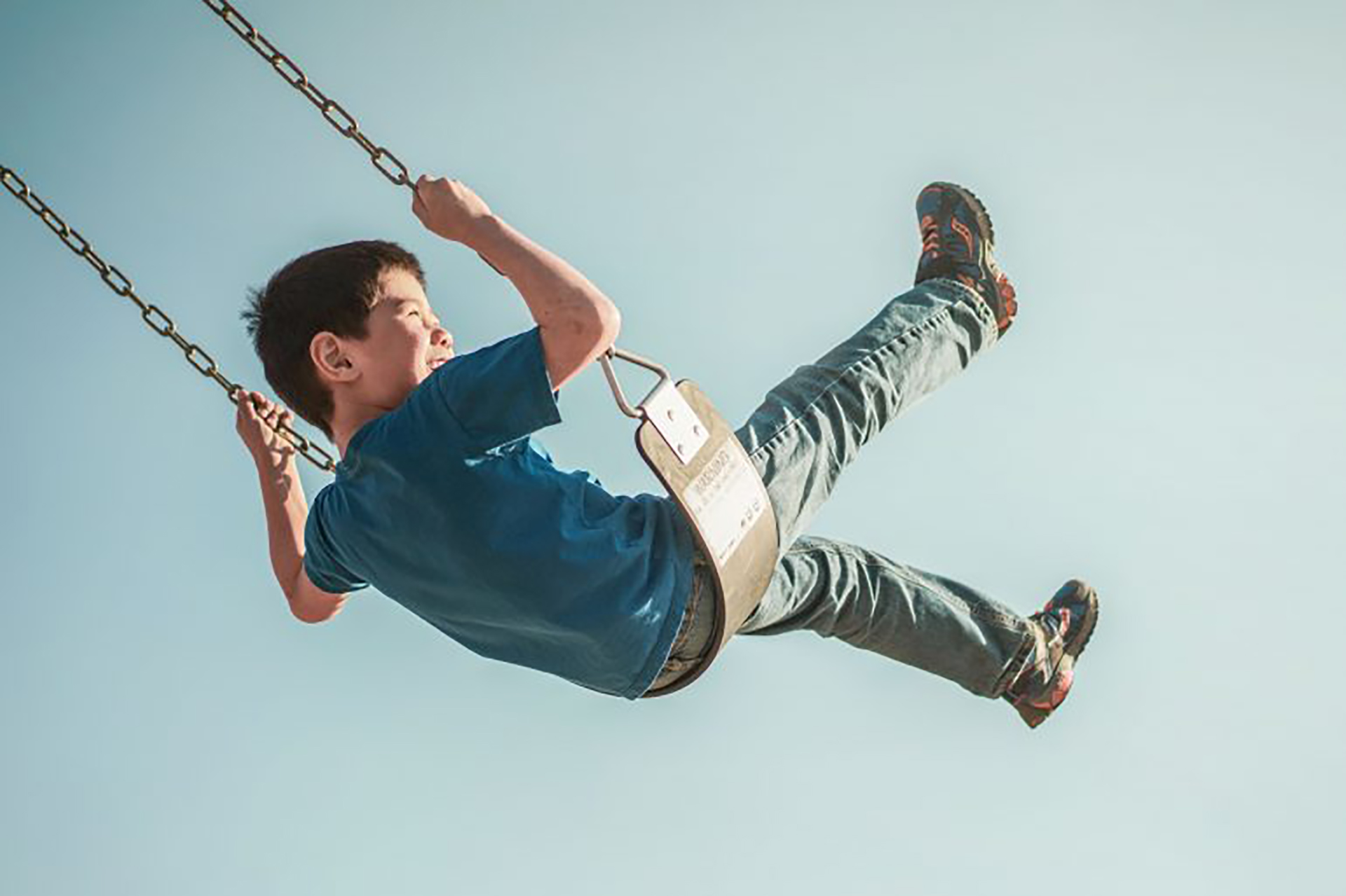 young male student high on a swing