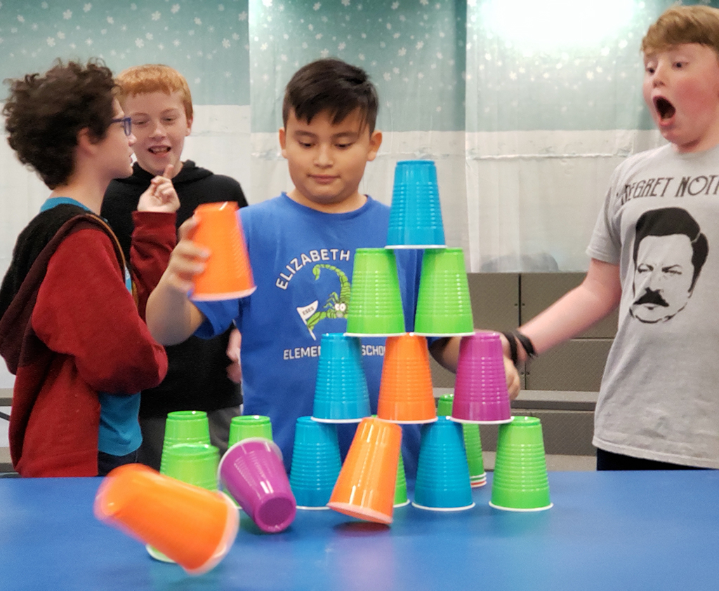 Four boys making a pyramid from solo cups.
