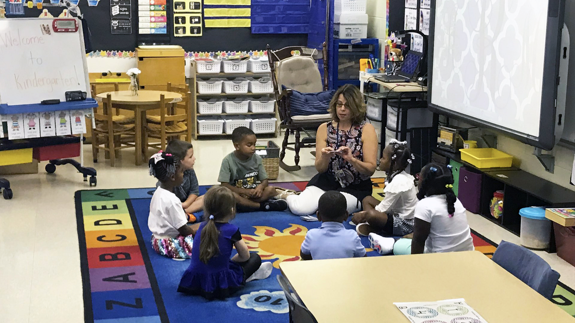 Teacher and students sitting on a rug in a circle as she shows them something.