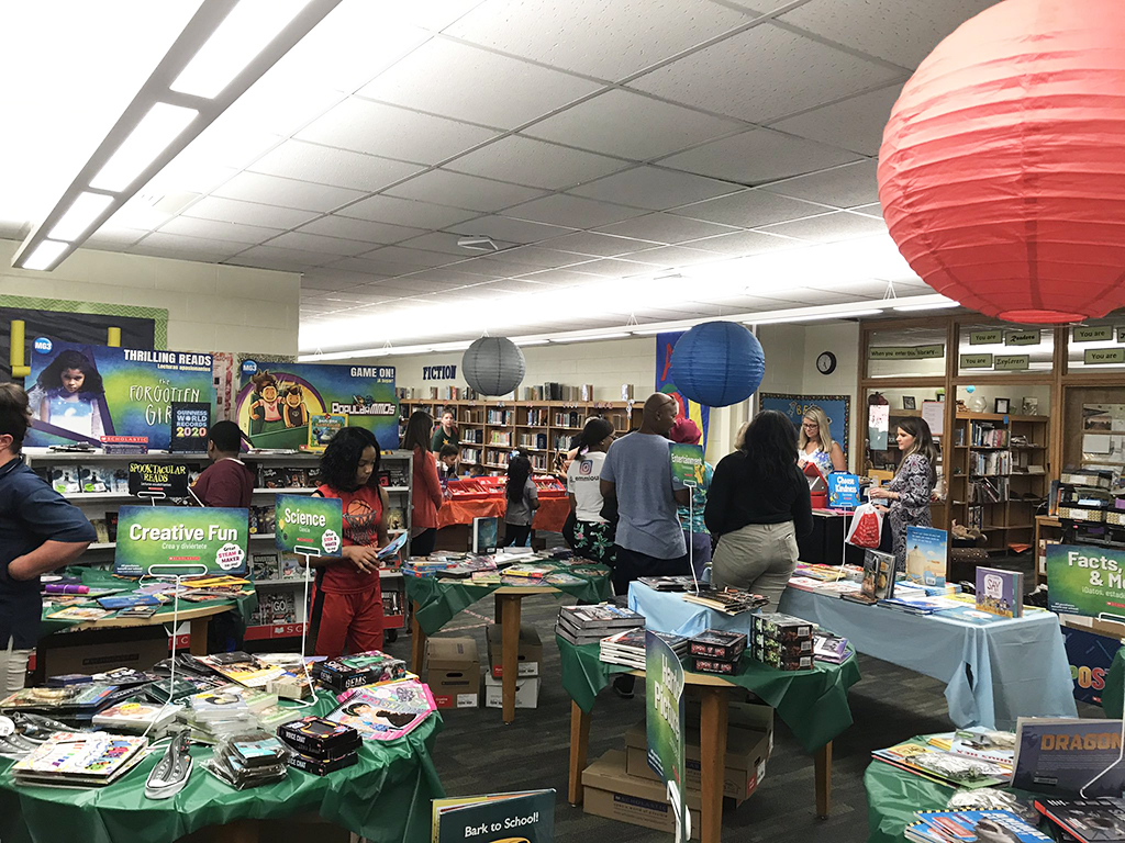 view of library during book fair with books all over the tables and students shopping