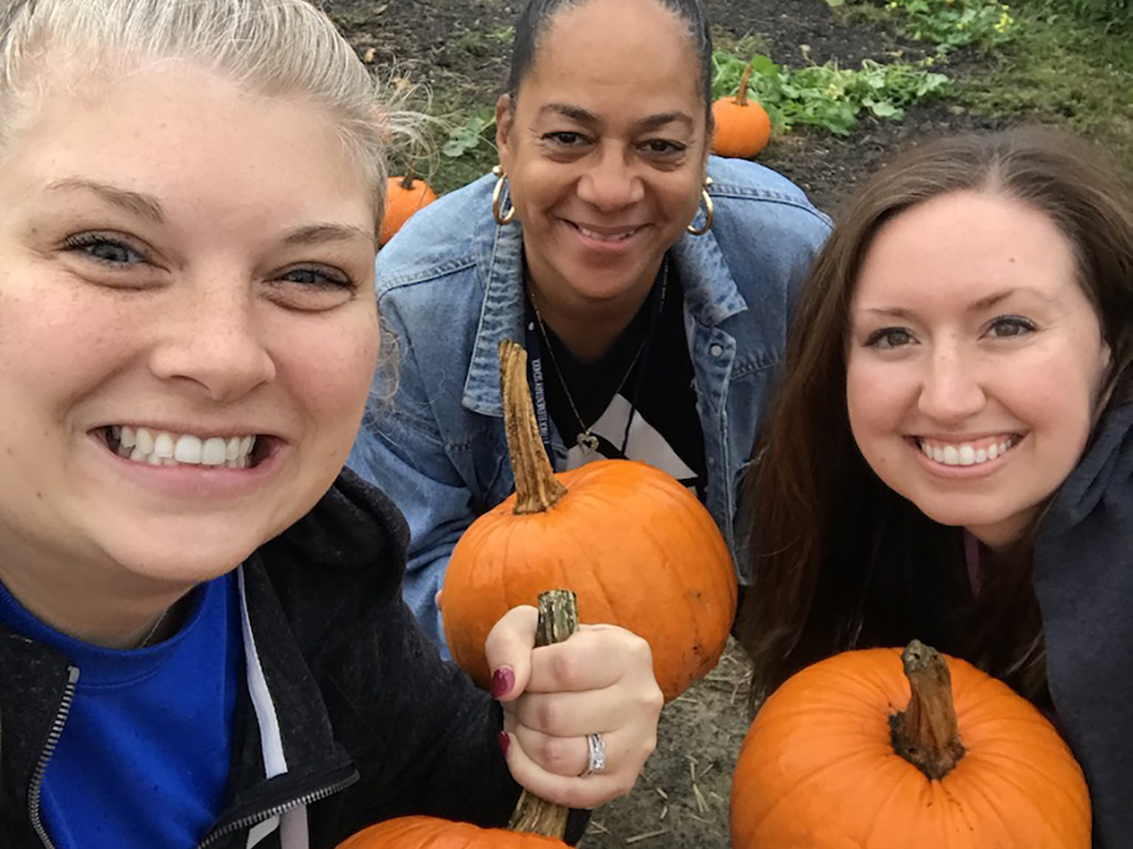 three female adults holding pumpkins standing in a pumpkin patch