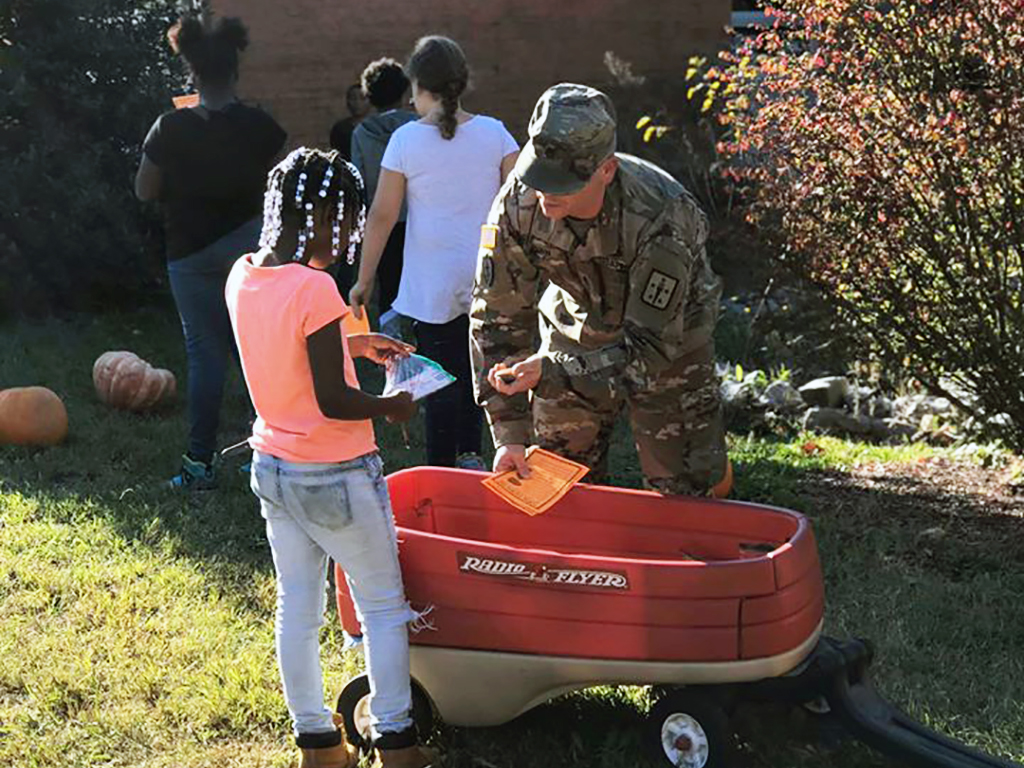 parents and soldier hand out pumpkins to students from a wagon outside.