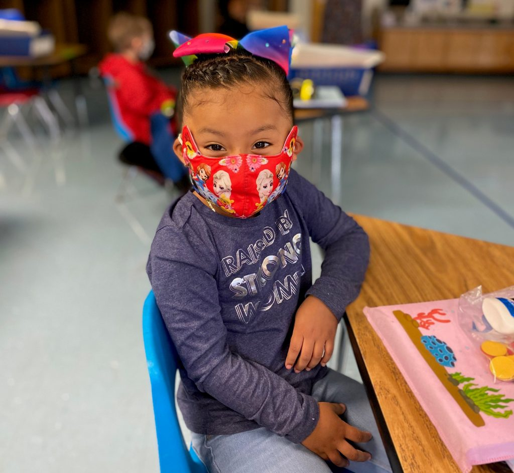 Child in class wearing medical mask