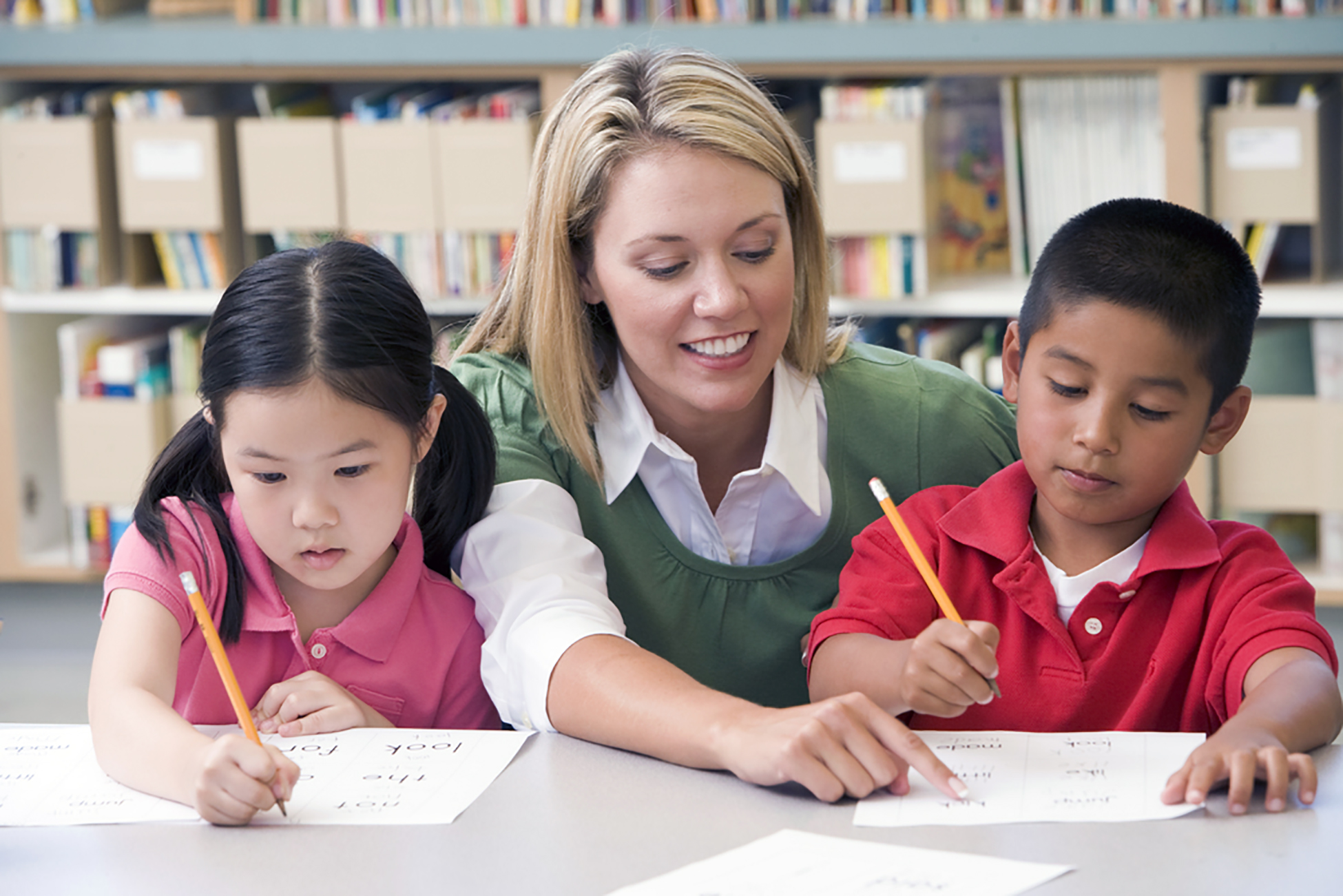 teacher at table helping two students to write