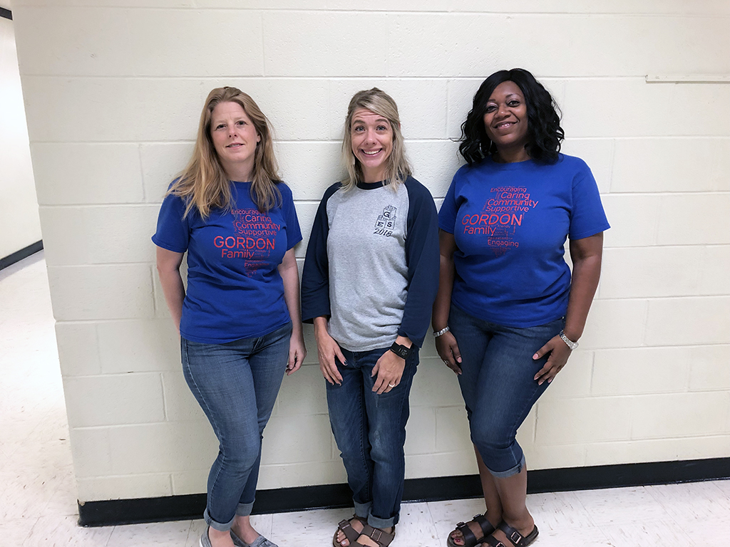 Three teachers lined up to pose for a photo