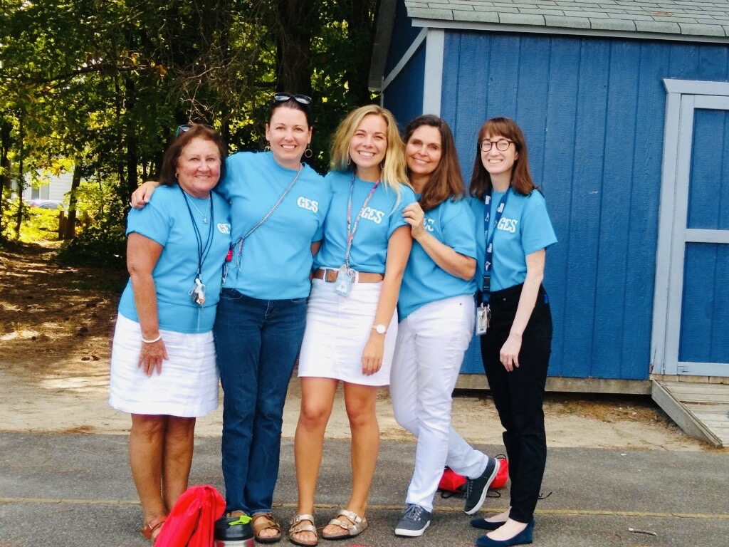 Five teachers in matching blue shirts line up for a photo.