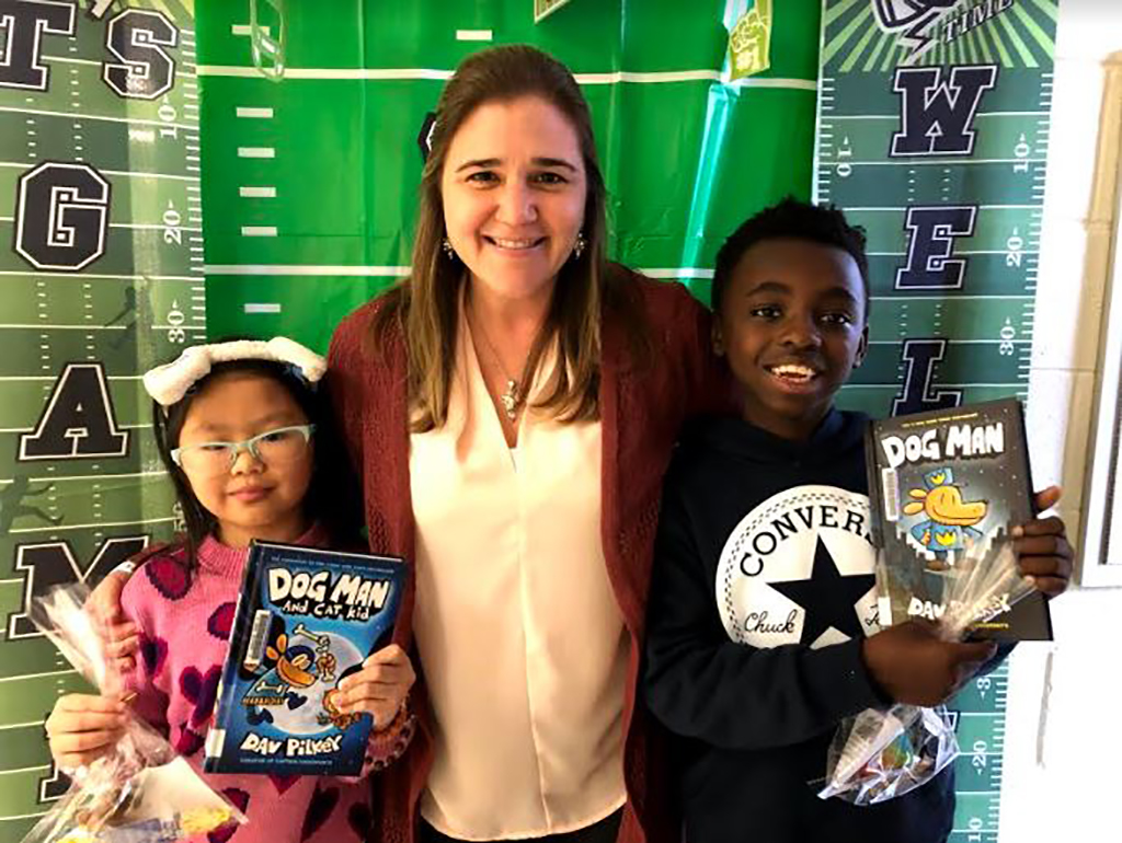 Librarian and two students holding up their books in front of a football field backdrop